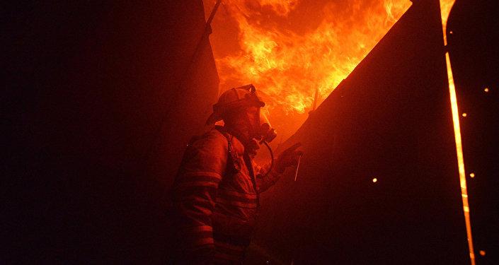 Пожарный тушит огонь