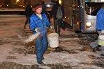 Сотрудник посыпает тротуар песчано-соляной смесью