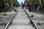 Беженцы пересекают железнодорожную ветку
