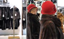 Покупательница во время примерки шубы в магазине