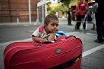 Мальчик ждет родителей возле берлинского офиса для беженцев