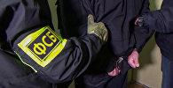 Супрацоўнікі Федэральнай службы бяспекі РФ канваююць затрыманага, архіўнае фота