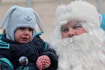 Дед Мороз разговаривает с ребенком в городском парке
