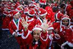Дети в костюмчиках Санта-Клауса в благотворительном параде в португальском Лиссабоне