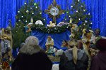 Прихожане костела святых Симеона и Елены молятся у яслей младенца Иисуса перед началом рождественской службы