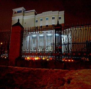 Беларусы нясуць кветкі да будынка пасальства Расіі ў Мінску