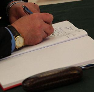 Дипломаты делают записи в книге соболезнований в посольстве РФ в Минске
