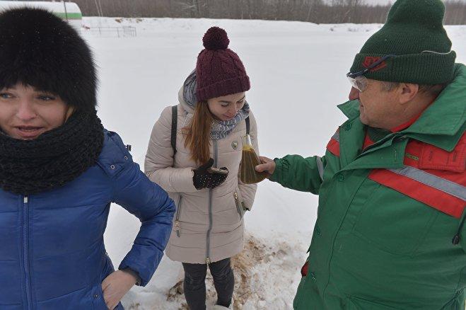 Василий Ласица, оператор по добыче нефти и газа, показывает журналистам добытую нефть