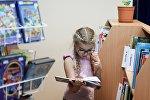 Девочка читает в библиотеке