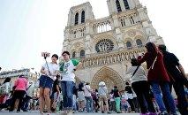 Туристы делают селфи перед собором Нотр-Дам в Париже