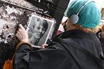 Женщина клеит портрет Дэвида Боуи возле его аппартаментов в Нью-Йорке