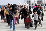 Семья мигрантов сходит на берег в сицилийском порту
