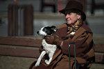 Женщина сидит на скамейке с собакой на руках