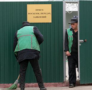 Заключенные подметают территорию перед входом, где принимают посылки и передачи для осужденных, архивное фото