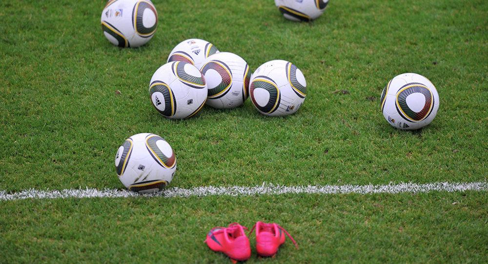 Футбольные мячи на поле.
