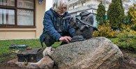 Скульптар Уладзімір Панцялееў ўсталёўвае жабку-падарожніцу пасля рамонту