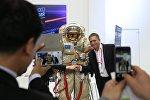 Посетитель фотографируется со скафандром на стенде Роскосмоса