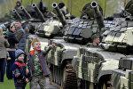 Минчане наблюдают за прохождением колонны военной техники по улицам Минска во время репетиции парада в честь 70-летия Победы