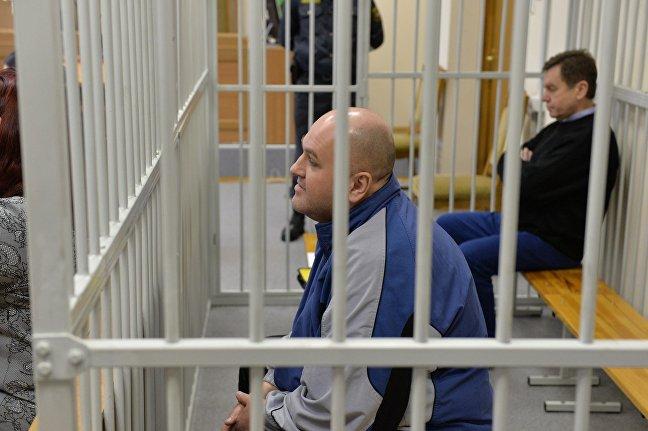 Подсудимый Андрей Турченко, за ним также за решеткой - председатель Белкоопсоюза Сергей Сидько