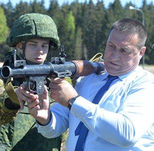 Салдат тэрміновай службы дзеліцца з намеснікам кіраўніка камісіі Уладзімірам Базанавым вопытам валодання РПГ-7.