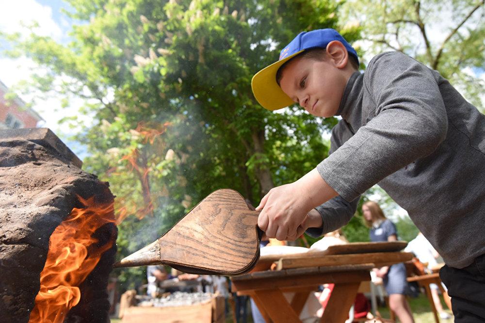 Студэнты гістарычнага факультэта пабудавалі паходную печ. У руках хлопчыка - мяхі для раздзімання агню.