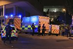 Armed police positioned near emergency vehicles after reports of an explosion at the Manchester Arena during an Ariana Grande concert in Manchester, England Monday, May 22, 2017.