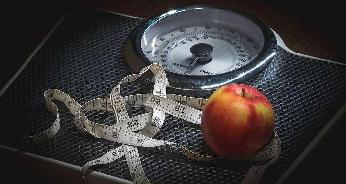 Весы, сантиметр и яблоко, архивное фото