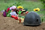 Цветы возле пробитой каски времен Великой Отечественной, архивное фото