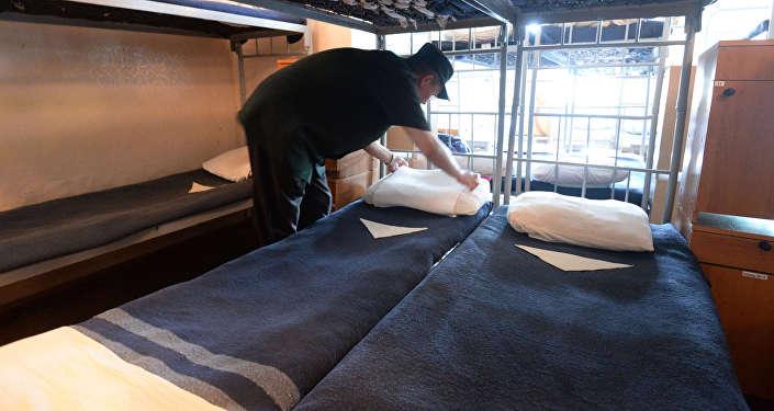 Заключенный заправляет постель, архивное фото