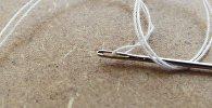 Швейная игла с ниткой