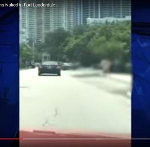 Видеофакт: грабитель банка бегал голым по улице и швырял деньги
