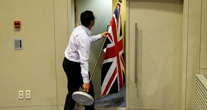 Мужчина выносит британский флаг, архивное фото