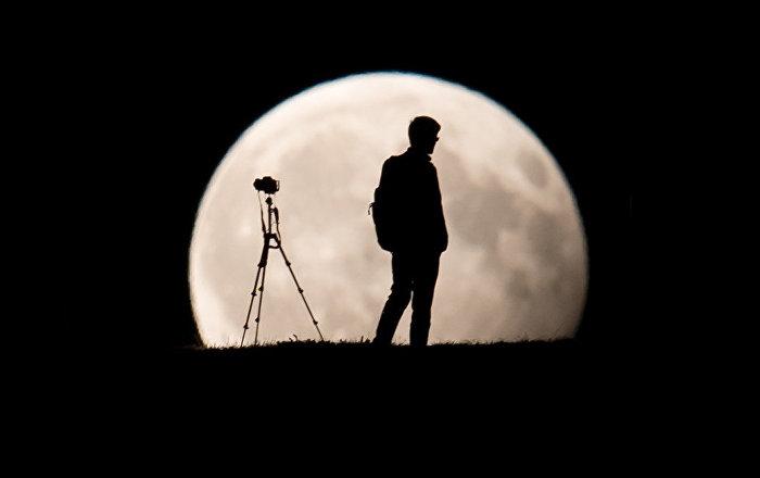 Фотограф снимает частичное лунное затмение в Мюнхене, Германия