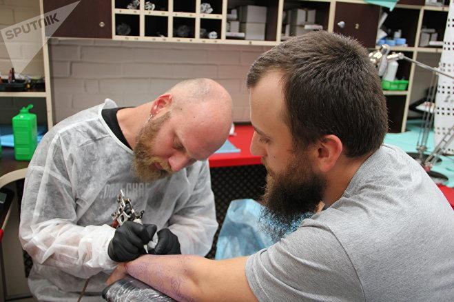 Тату-мастер Алесь Таболич делает татуировку