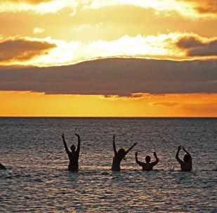 Нудисты отдыхают на пляже, архивное фото