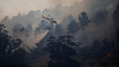 Вертолет в небе над горящей Португалией