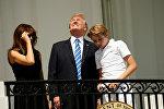 Президент США Дональд Трамп наблюдает солнечное затмение с первой леди Меланией и сыном Барроном с балкона Трумэна в Белом доме в Вашингтоне
