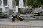 Мальчик катается на машинке у фонтанов
