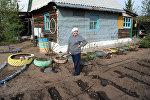 Женщина-дачница возле своего дома