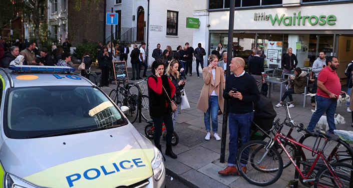 Люди стоят на улице возле станции метро Parsons Green в Лондоне