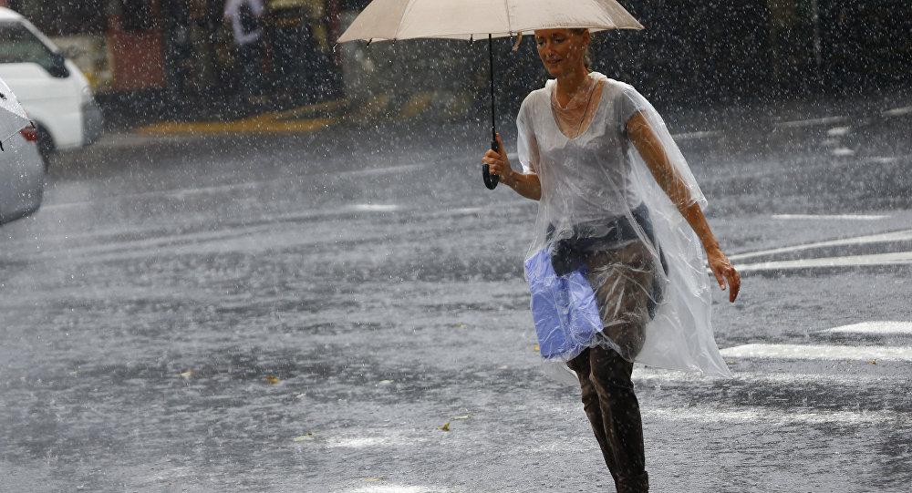 Японка под зонтом во время сильного дождя, архивное фото