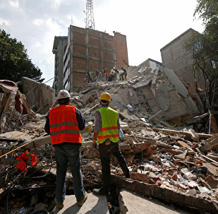 Спасатели и рабочие на месте разрушенного землетрясением дома в Мехико