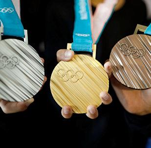 Молодежь позирует для фотографий с медалями для зимних Олимпийских игр в Пхенчхане 2018 года во время церемонии презентации в Сеуле, Южная Корея