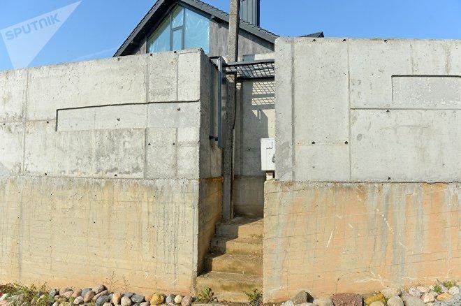 Бетонная стена достигает семи метров в высоту и скрывает все, что происходит на участке Грабовского