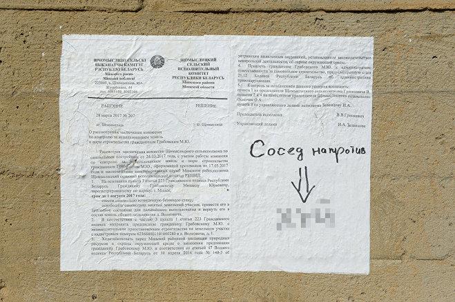 На стене соседи прикрепили решение местного сельсовета о сносе ограждения, на документе кто-то оставил ответ