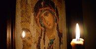 Горящая свеча на фоне вышитого изображения Казанской иконы Божьей матери
