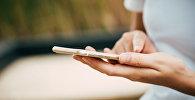 Девушка держит смартфон, архивное фото