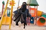 Саудовская женщина на качелях, архивное фото