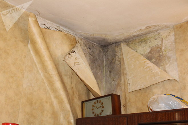 В квартире на последнем этаже отклеились обои и почернел потолок и стены