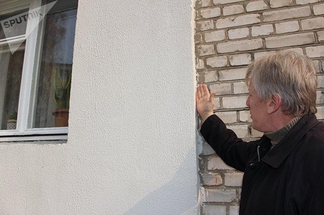 Вадим Ерошов показывает запачканные краской и штукатуркой стены, на окнах нет отливов